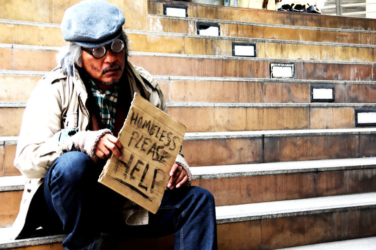 Beggar holding placard while sitting on steps