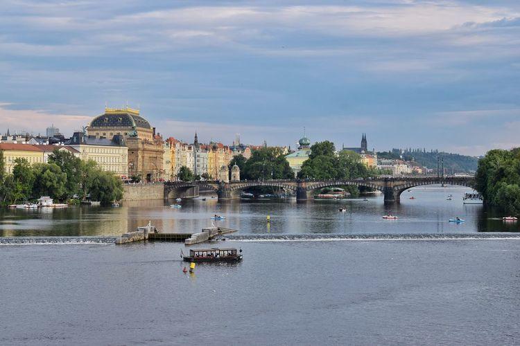 Bridge over river against buildings in city