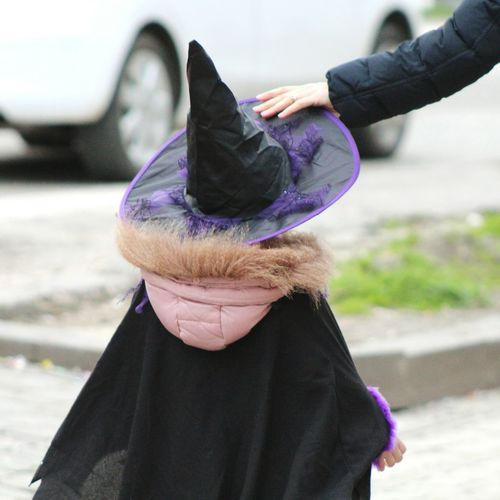 Rear view of girl witch costume walking on footpath