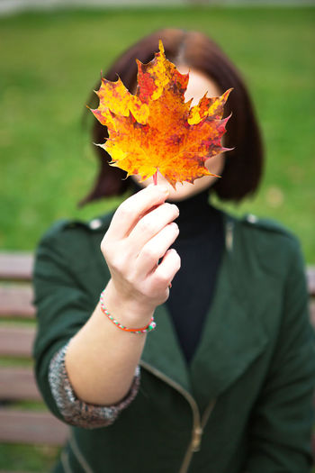 Close-up of woman holding maple leaves