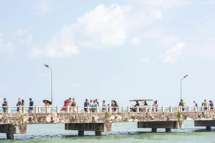 People walking on pier by sea against sky