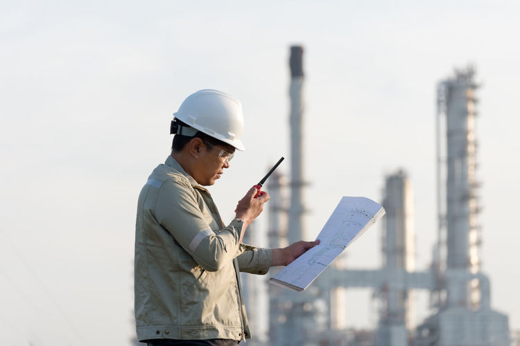 Side view of worker holding blueprint and walkie-talkie near factory