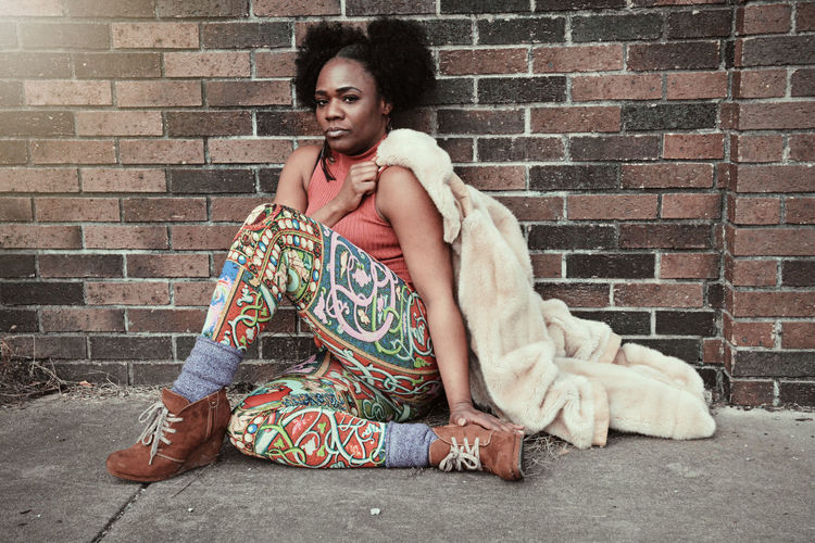 Portrait of mid adult woman sitting on footpath against brick wall