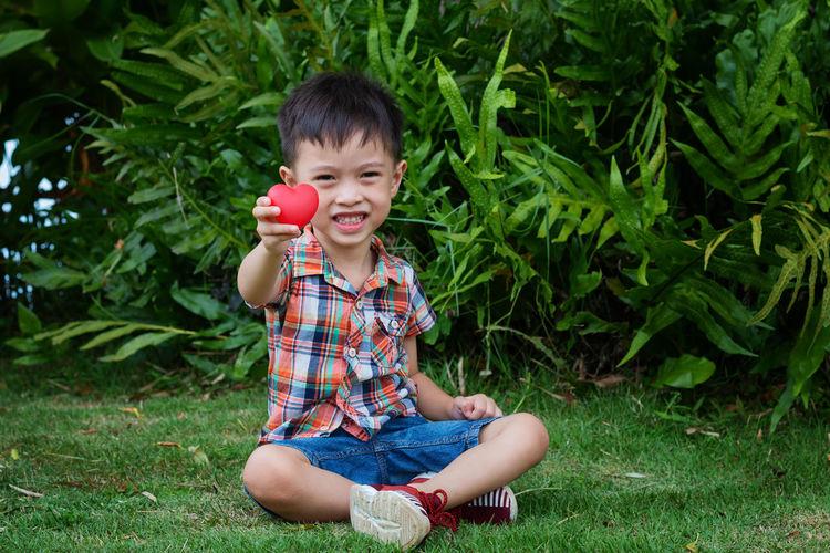 Portrait of boy holding heart shape on field