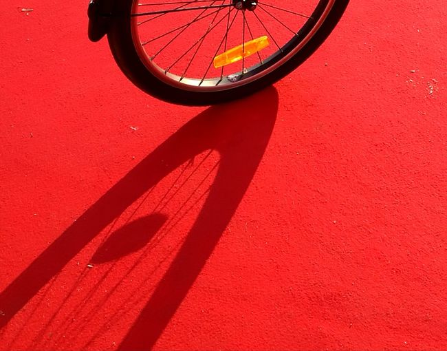 Close-up of bicycle on red wall