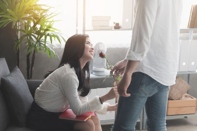 Picture of young man surprising woman with flowers Two People Casual Clothing Holding Young Women Indoors  Lifestyles Young Adult Togetherness Adult Bonding Women Sitting Leisure Activity Refreshment Love Glass Couple - Relationship Valentine's Day  Love Rose - Flower Flower Surprise Flirting Dating Smiling