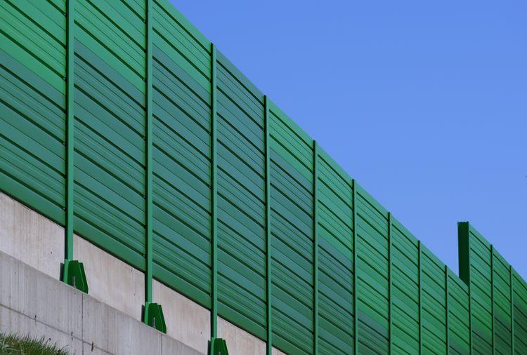 A green sound-absorbing barrier under a blue sky