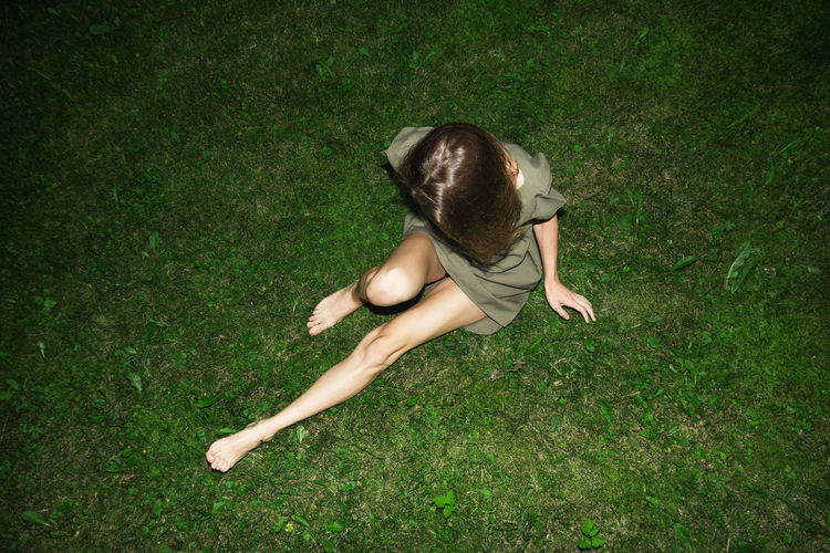Directly Above Shot Of Young Woman Sitting On Field