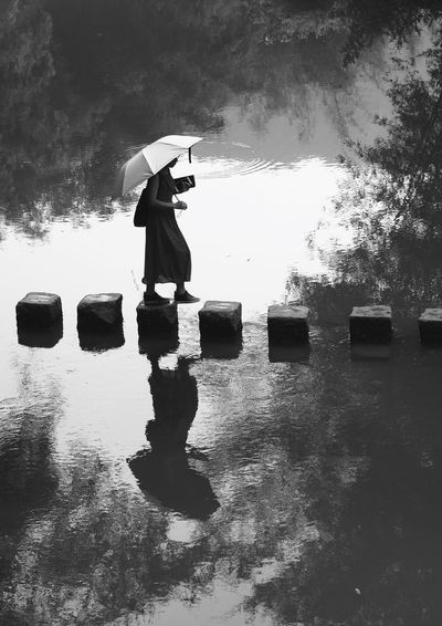 Short-Cut to Work Hezhou China People Ancient Town Of Hezhou Blackandwhite Silhouette Trees Nature People Umbrella Sunny Reflection Step By Step Walking Water Wet Real People Reflection One Person Umbrella Nature Day Outdoors