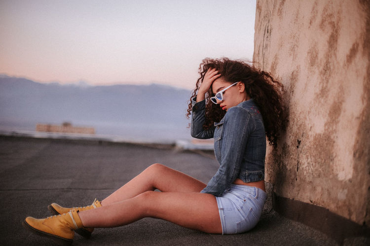 Side View Of Woman Sitting Against Wall During Sunset
