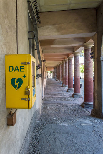 Meldola, Italy, close up of an automated external defibrillator (in italian abbreviation is DAE) place on public street Architecture Built Structure No People Building Sign In A Row Communication Architectural Column Direction The Way Forward Yellow Arcade Corridor Day Indoors  Text Transportation Diminishing Perspective Ceiling Concrete