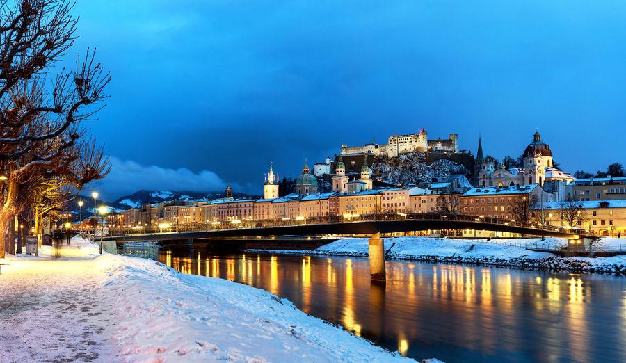 Illuminated bridge over river against blue sky during winter