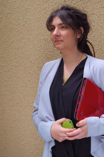 Young businesswoman holding file and phone looking away standing against wall
