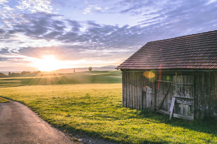 Old Wooden House On Field Against Sky During Sunset