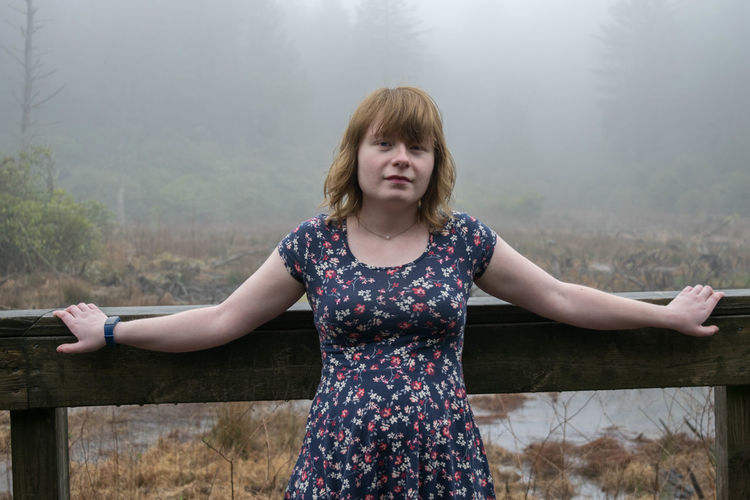 Young woman standing against railing in forest