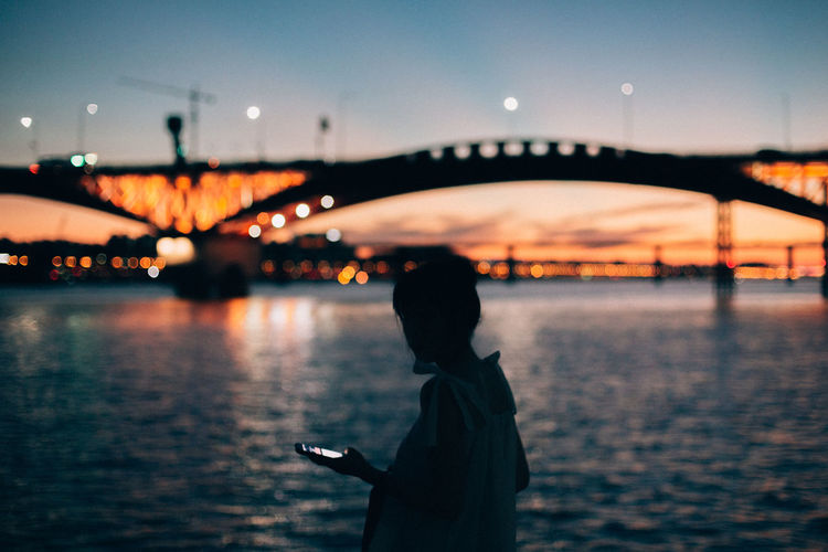 Side view of woman with smart phone walking by river in city during sunset