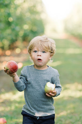 Full length of boy holding apple standing outdoors