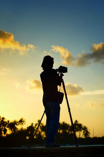 Scenic view of photographer silhoutte on the sunset background. Wallpaper Background Malaysia Beach Color Photography Photographer Men Alone Action Action Shot  Full Length Men Standing Silhouette Holding Photography Themes Tripod Filming Sky Camera Photographing Taking  Photographic Equipment Camera - Photographic Equipment
