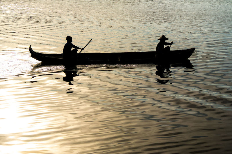Silhouette people sailing on boat in river during sunset