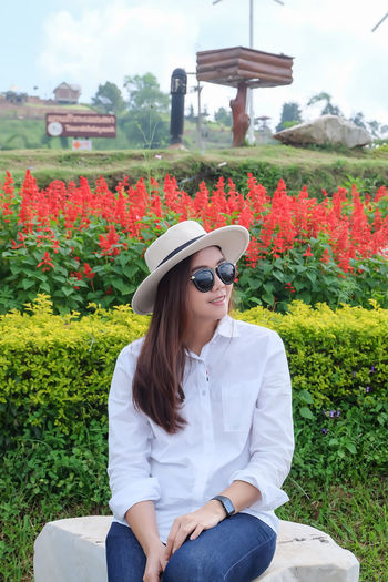 Asian young woman traveling wearing white shirt, jeans, white hat and sunglasses in smiling Fashion Adult Asian  Autumn Casual Freshness Happy Hat Lifestyle Sunny Travel Cheerful Day Female Flower Garden Hipster, Nature One Person Outdoors Portrait Relaxation Spring Young Adult Young Women