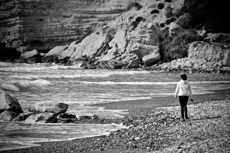 Rear view of woman standing on rock by sea