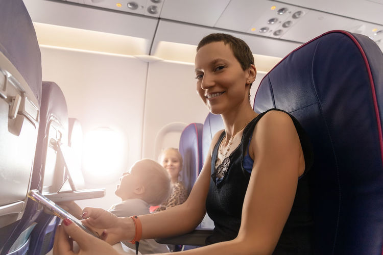 Portrait of smiling mother sitting at airplane