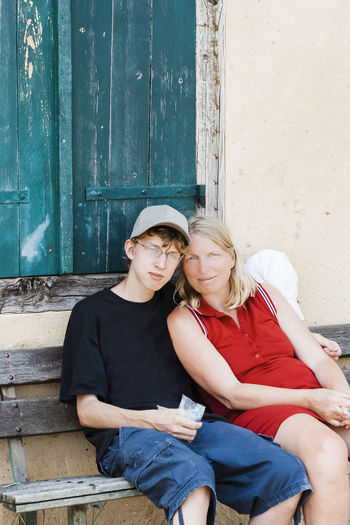 Portrait of mother and son sitting on bench against window