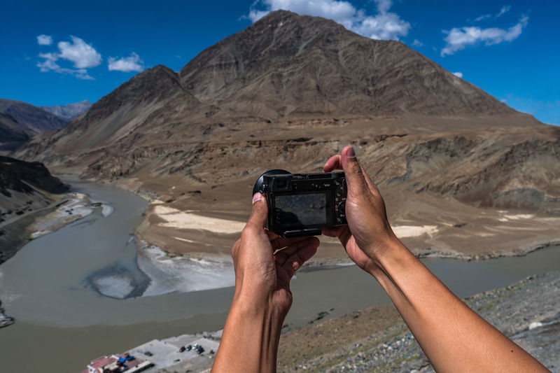 Midsection of person photographing camera on mountains