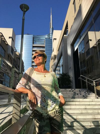 Happy Woman Standing On Steps Against Modern Buildings In City