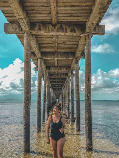 Woman in swimsuit standing under bridge