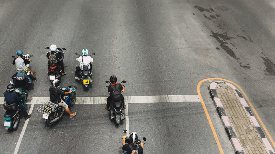 High Angle View Of People Riding Motorcycles On Road