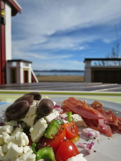 Greek salad in plate on table against cloudy sky during sunny day