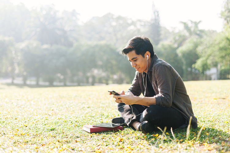 Man using smart phone while sitting at park