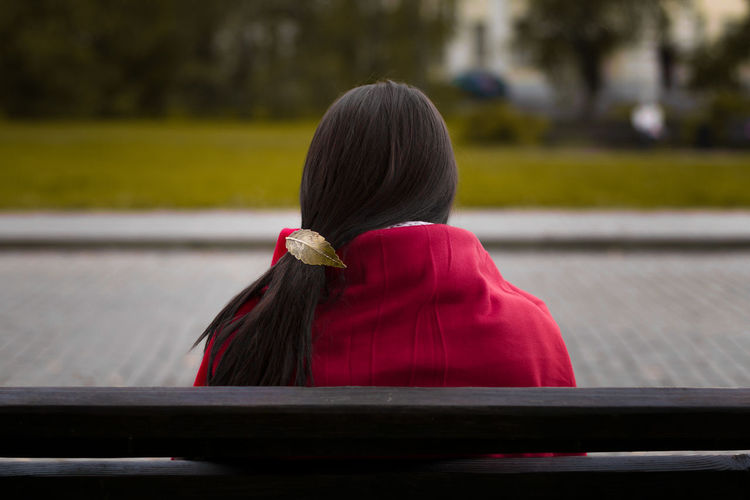 Rear View Of Woman Sitting Outdoors