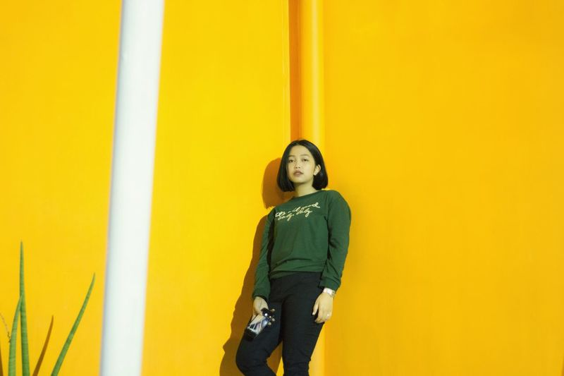 Portrait of woman standing against yellow wall