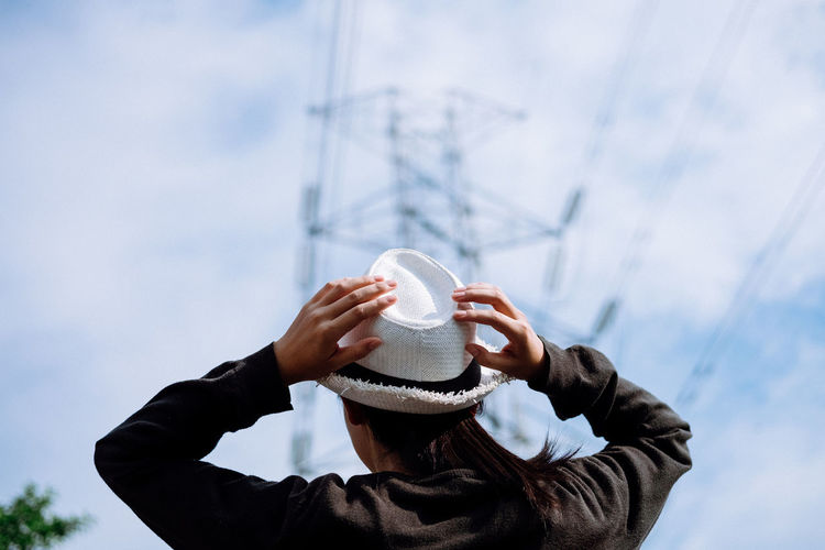 Close-Up Of Woman Holding Hat Against Sky