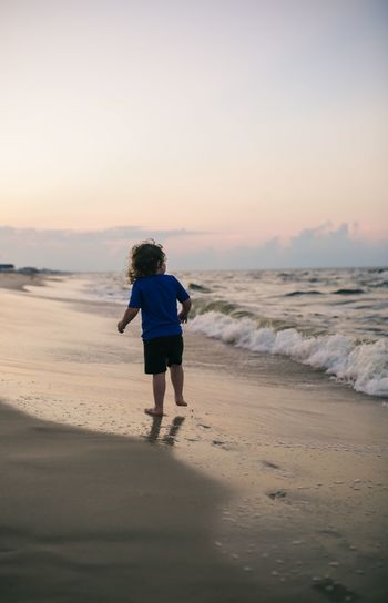 Seashore evening Childhood Beach Gulf Coast Summer Vacation Summer Boy Ocean Alabama Travel Fort Morgan Beach Sea Land Water Full Length Real People One Person Sky Rear View Lifestyles Leisure Activity Sunset Horizon Over Water Beauty In Nature Sand Horizon Nature Scenics - Nature Outdoors 2018 In One Photograph