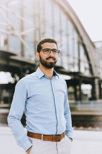 Portrait of smiling Syrian refugee man Arabian Business Confidence  Glasses Man Middle East Proud Refugee Stylish Syria  Syrian Refugees Travel Traveling Arabic Businessman Job Portrait Professional Railroad Station Refugees Style Syrian Syrian In Germany Transportation Young Men