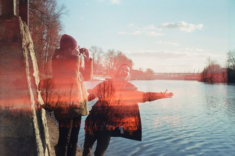 Double exposure of people standing by river and silhouette trees against sky