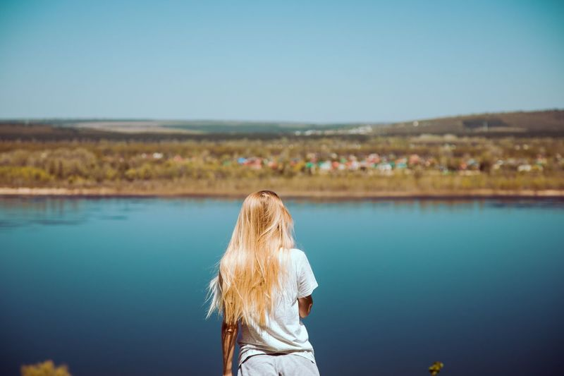 Rear view of woman standing against river