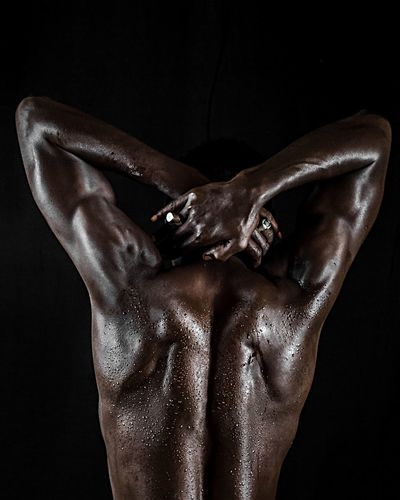 Rear View Of Shirtless Muscular Man With Sweat Standing Against Black Background