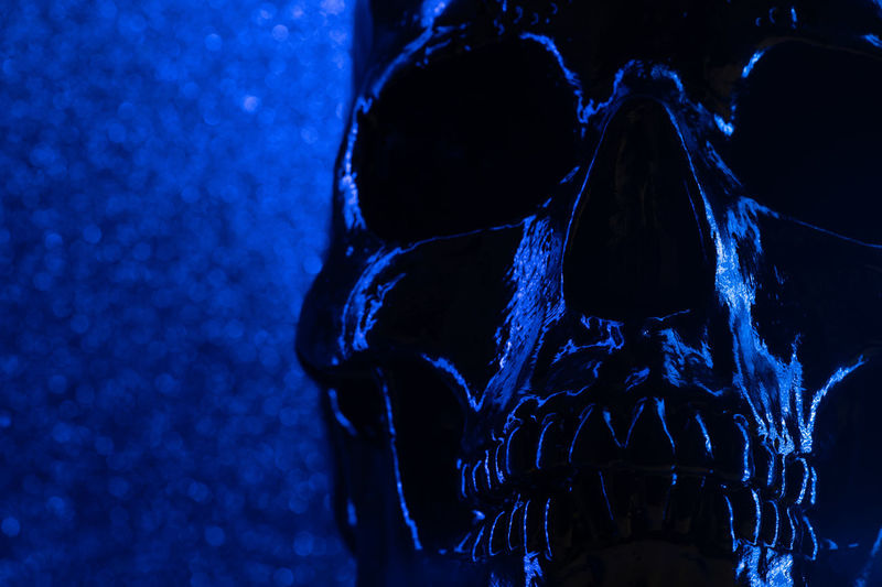 Human blue skull on dark background with bokeh. Concept of fear, death and horror, Halloween celebration. Spooky and sinister. Close-up Indoors  Human Body Part Human Skeleton Blue Human Skull Bone  Spooky Focus On Foreground Dark Human Bone Skeleton Illuminated Body Part Fear Night Lighting Equipment Horror Single Object