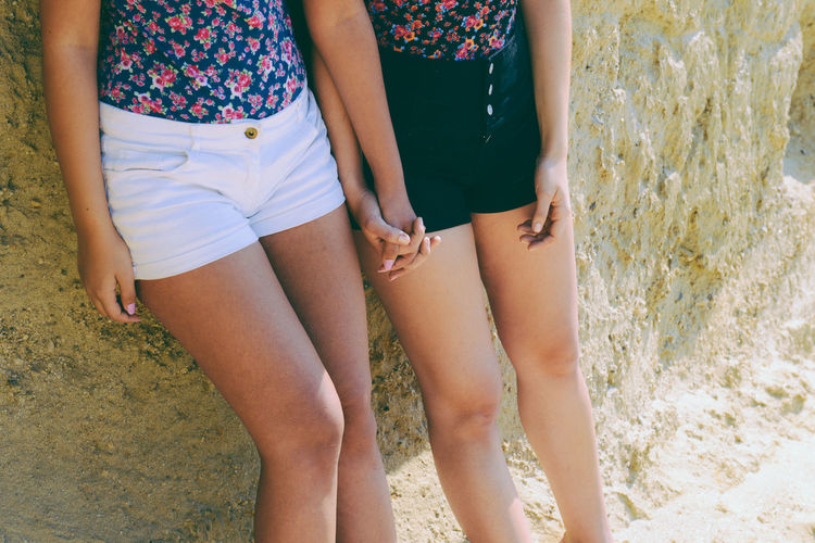 Midsection Of Friends Holding Hands While Leaning On Wall