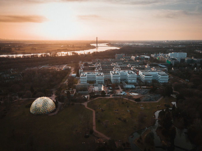 High angle shot of townscape against sky at sunset with a dome greenhouse