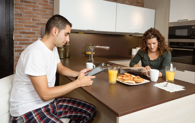 Happy young couple reading news in a digital tablet and newspaper while having breakfast on the home kitchen Family Fruit Girlfriend Thirties Relaxing Husband Boyfriend 30s Wife Relationship Adult Lifestyle Interior Love Cup Caucasian Healthy Two Coffee Glass Orange Girl Juice Meal Drink Together Young Woman Kitchen Man Indoors  Food Morning Technology Newspaper Digital Tablet News Smiling Cheerful Happiness Smile Happy Male Home People Female Couple Breakfast
