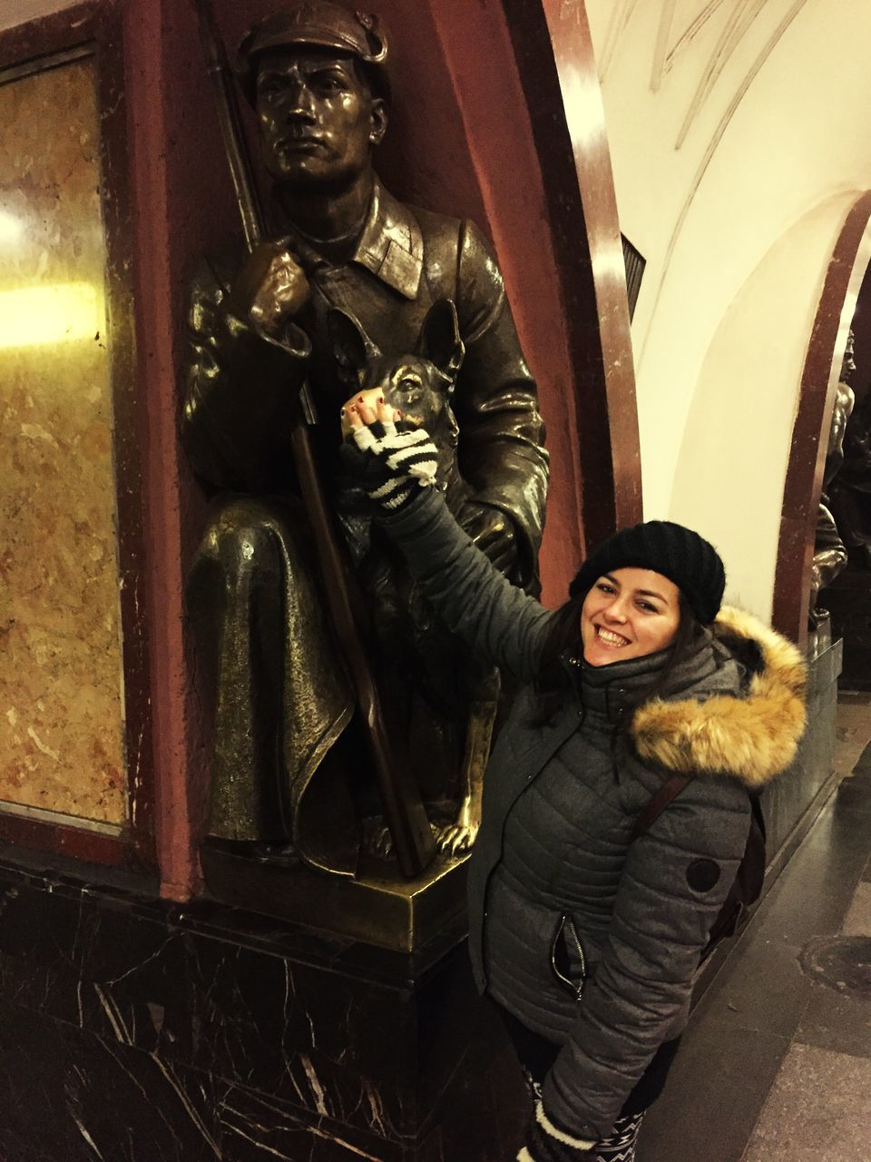 real people, smiling, statue, lifestyles, human representation, front view, happiness, one person, looking at camera, jacket, sculpture, indoors, portrait, leisure activity, young women, standing, young adult, night, warm clothing