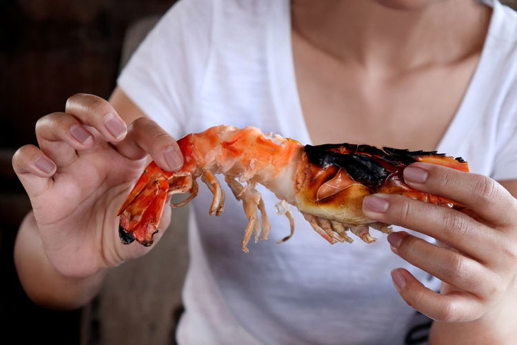 Midsection of woman holding shrimp