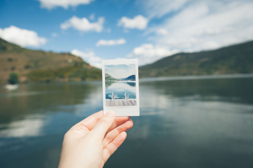 Beauty In Nature Close-up Cloud Cloud - Sky Cropped Day Focus On Foreground Holding Human Finger Lake Leisure Activity Lifestyles Mountain Mountain Range Nature Outdoors Part Of Person Personal Perspective Scenics Sky Tranquil Scene Tranquility Unrecognizable Person Water