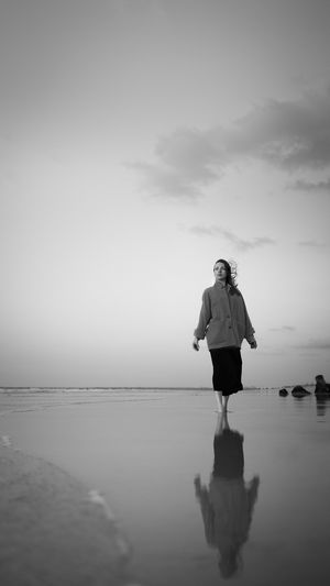 Woman standing on sea against sky