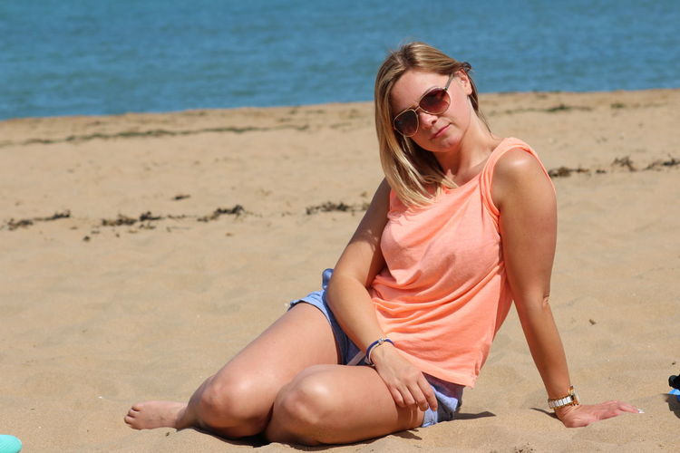 Portrait of mid adult woman wearing sunglasses while sitting at beach